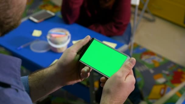 Skupina lidí debaty v dílně a muž hospodářství smartphone s zelená obrazovka