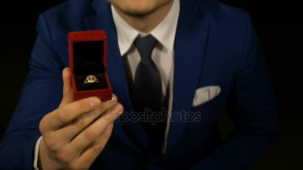 Man kneeling with engagement ring box in hand for marriage proposal