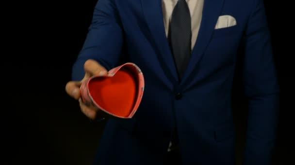 Muž slaví Valentýn a nabízí svou přítelkyni dárek ve tvaru srdce