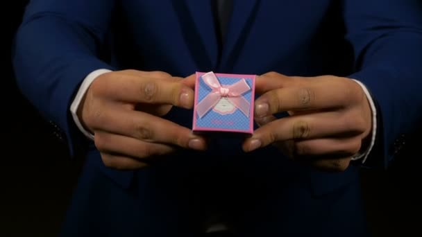 Ruce muže ukazující a drží malý dárek šperky box
