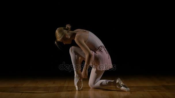 Ballerina bindet ihre Spitzenschuhe und bereitet sich auf die Show vor