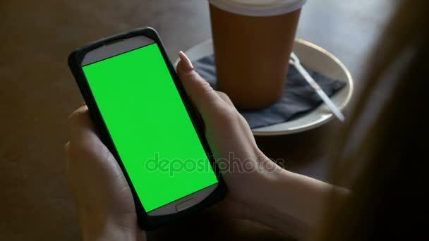 Closeup ruce ženy držící chytrý telefon s chroma klíč fabion v kavárně