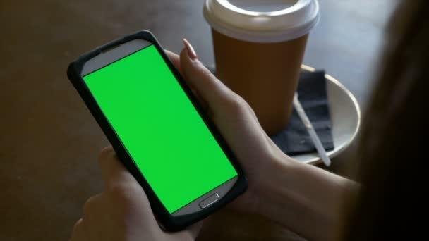 Student dívka studie pomocí chytrého telefonu v režimu na výšku s kávou na stůl