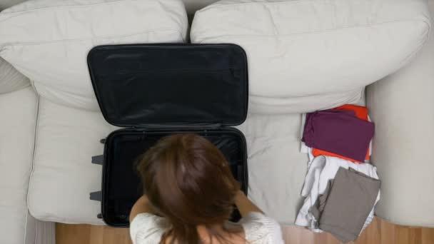 Mladá žena pečlivě připravuje cestovní tašku pro letní výlet
