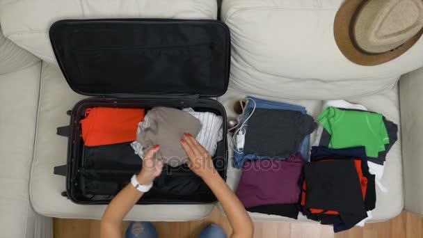 Pohled shora mladé ženy uspořádání oblečení do kufru