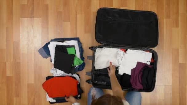 Pohled shora atraktivní ženy stojící na dřevěnou podlahu a vybalování oblečení z kufru
