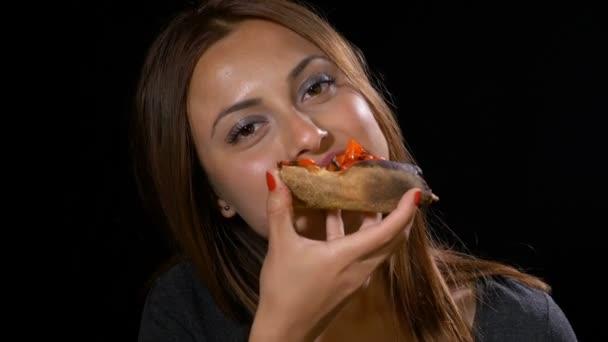 Hezká dívka nezdravé, jíst pizzu a usmívá se