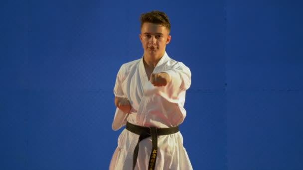 Karate gyerek harci gyakorolja a lyukasztó és virul technikák a dojoban edzés közben