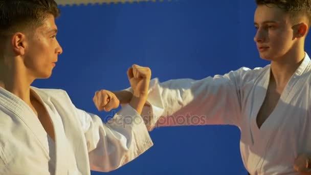 Két fiatal felnőttek kimonó karate edzés és gyakorlás blokkoló technikák
