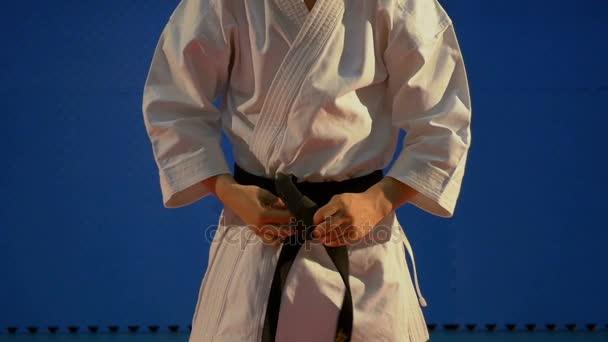 ultimo sconto tra qualche giorno nuovo stile del 2019 Chiuda in su dell'uomo legare il nodo della cintura nera sulle  apparecchiature di kimono karate speciale al rallentatore