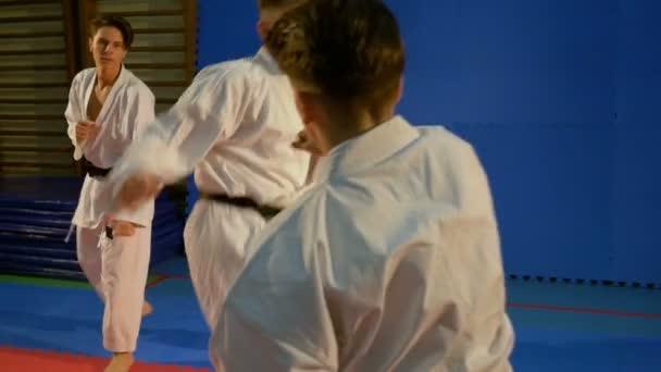 Tři mladiství cvičí karate a zapojení v bojové použití útoku a blokování techniky v tělocvičně