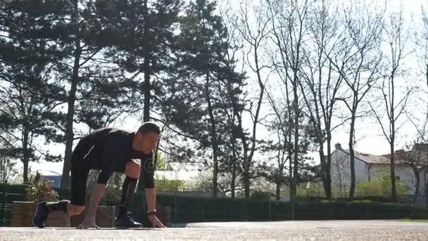 Zpomalený pohyb fit běžec běží od bloku počáteční pozici na trati