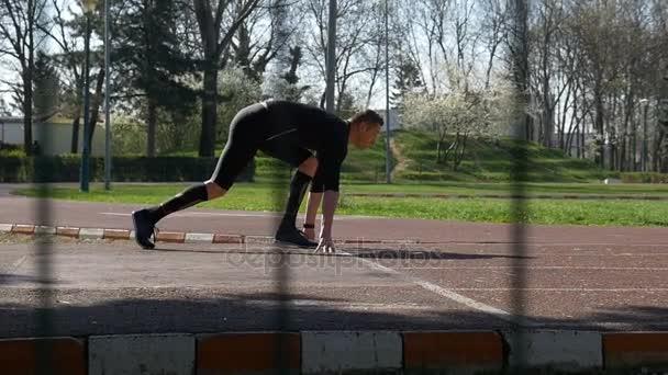 Atlet na startovní čáru od počáteční pozice bloku běžící na závodní dráze v ráno v pomalém pohybu