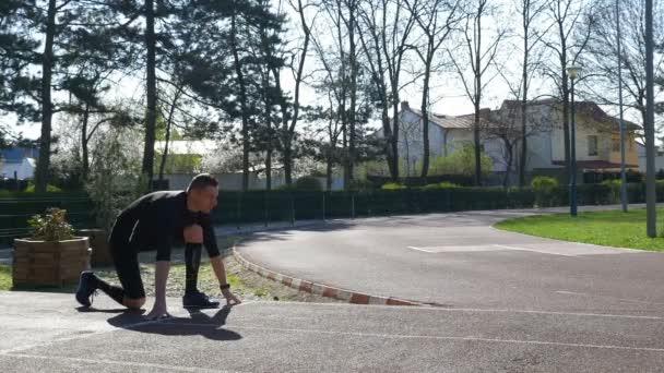 Mladý muž běžec na startovní čáře v bloku počáteční pozici na závodní trati v parku