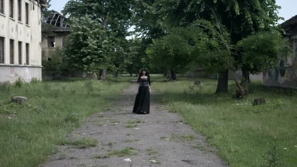 Young macabre woman with gothic black clothes and crown of ivy leaves walking among ruined buildings of an old mansion with evil expression face