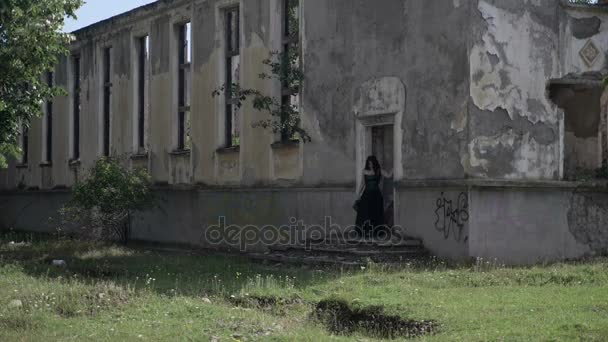 Ghost of beautiful young lady dressed in gothic black clothes exiting a haunted ruined palace