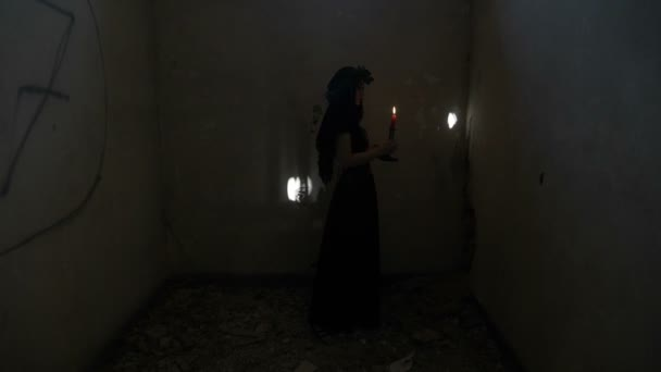Demonic gothic evil woman turning around holding a candle and angrily screaming in a dark abandoned room
