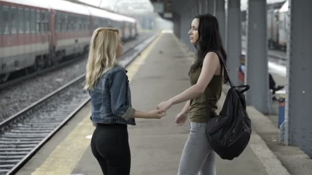 Sad young girls walking hand in hand in train station hugging before separation– stock footage