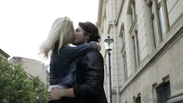 Passionate young couple kissing and embracing spinning around outdoor in the city