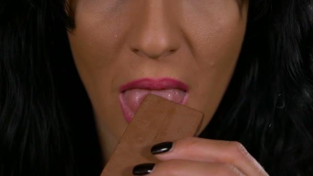 Nahaufnahme der jungen Frau, die süchtig nach Süßigkeiten essen eine braune Praline-Bar-Slow-motion