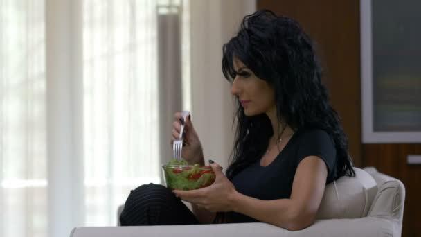 Atraktivní žena jíst mísu hlávkovým salátem a rajčaty zeleninový salát jídlo doma dívat na televizi