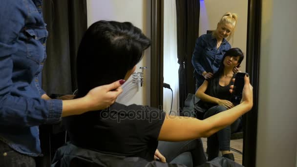 Young attractive woman taking selfie with her hairdresser at beauty salon