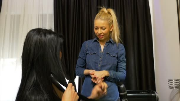 Hairstylist talks with her customer in hair salon