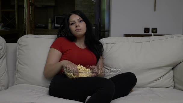 Unatkozó fiatal nő ül a kanapén, és pattogatott kukoricát eszik este Tv nézés közben