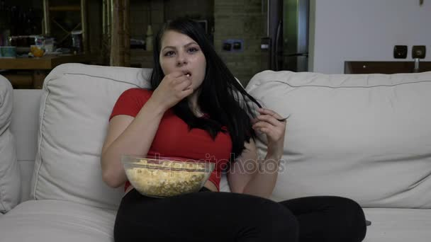 Tini ül a kanapén, és közben film néz és az érzés felháborodott pattogatott kukoricát eszik