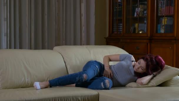 Junges Mädchen mit Menstruation Bauchschmerzen auf Couch zu Hause