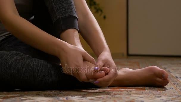 Primo piano della giovane donna a piedi nudi che massaggiare il piede slogato avendo sintomi dolorosi