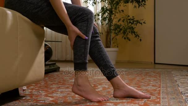 Mladá žena s svalová křeč masírovat její bolestným nohu