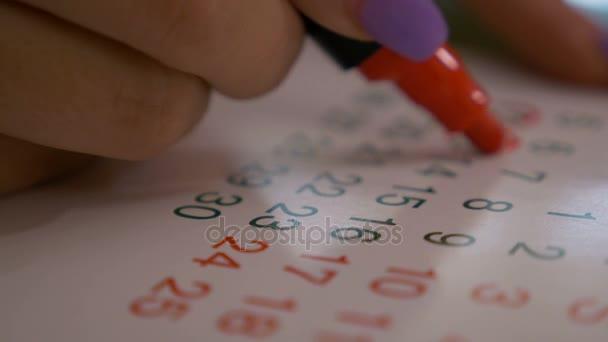 Closeup žena ruky označení data a dny v kalendáři s červenou značkou