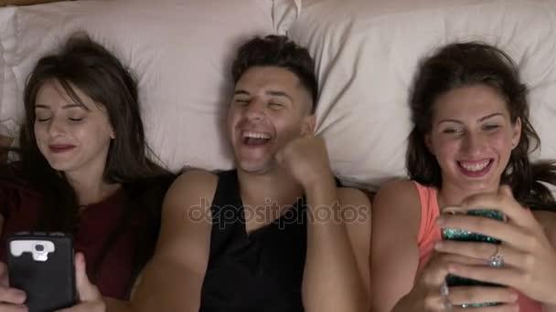 Fiatal ember ül a lányok nevettek, és pihentető az ágyban, hogy vicces arcok és okostelefon játék között