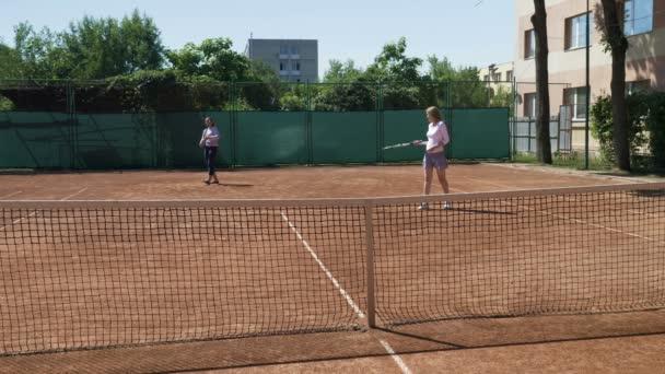 Dva přátelé dívka hrát tenis čtyřhra zápas vyhrál a těší jejich triumf