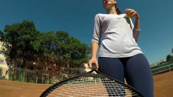 Akční z pohledu ženy držící tenisovou raketu v ruce na tenisový kurt sloužící míč