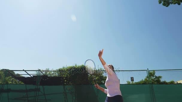 Tenisový hráč dívku udeří míč s raketou v pomalém pohybu