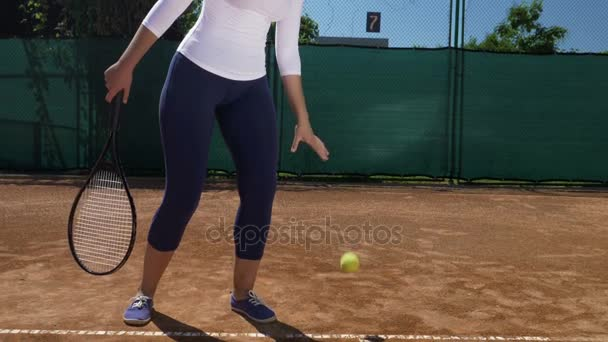 Detailní záběr ženy s tenisovou raketu v ruce a druhou rukou skákací míč na škváry