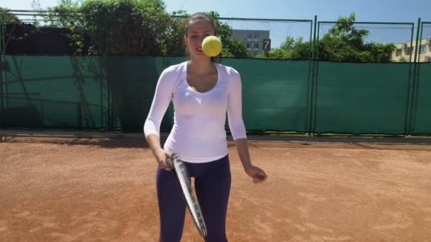 Radostné dívka vyvážení míče na tenisovou raketu na tenisový kurt