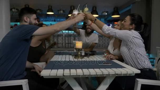 Fiatal baráti pirítás ital a bárban lounge ünnepli clink szemüveg, és miután egy nagy idő