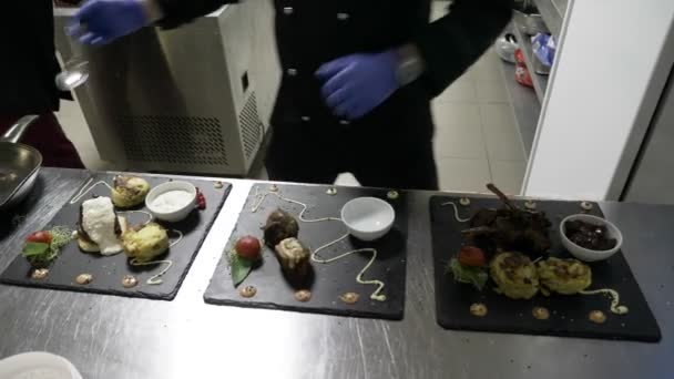 Male chef preparing three dishes in the kitchen of restaurant garnishing and decorating the plates