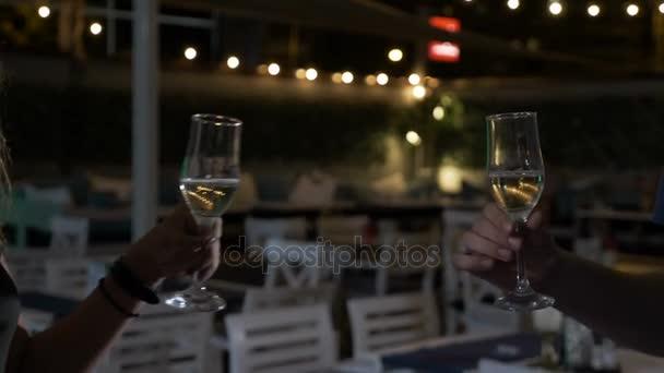 Usmíval se blondýnka opékání sklenku šampaňského s mladými muži a cinkání brýlemi