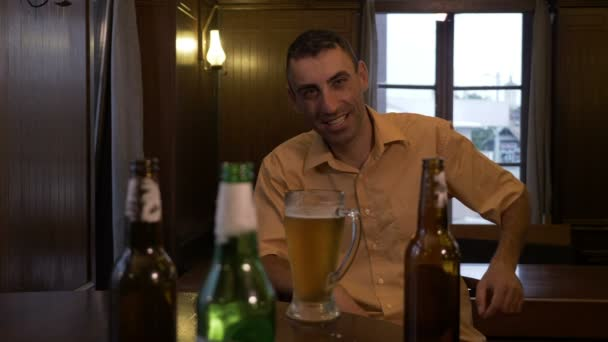 Man sitting at a bar with a glass of beer in front and cheers and drinks
