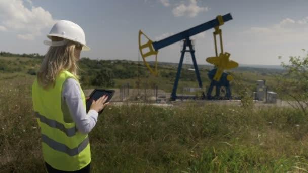 Předsedkyně inženýr ropy pomocí tablet pc zkontrolovat plán údržby pro olejové čerpadlo