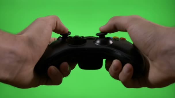 Young game player hands controlling joystick keys playing video game on green screen