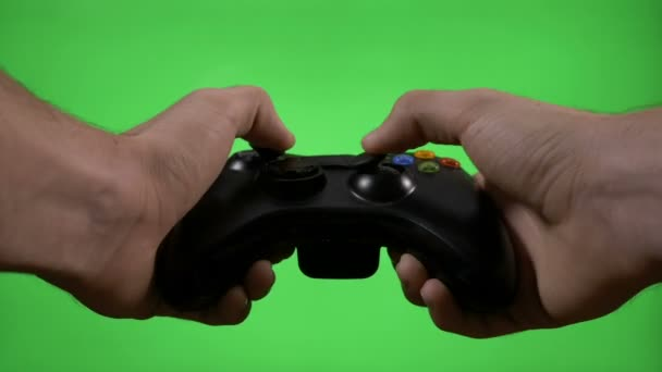 Frustrated angry gamer playing video game match on green screen shaking game  remote controller losing game