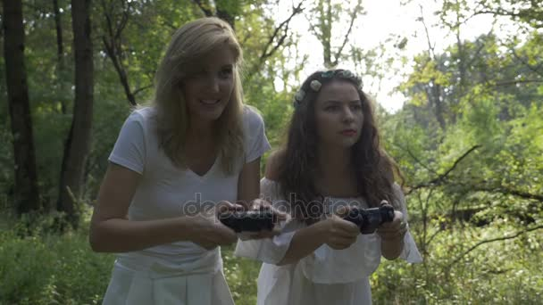 Two girl friends holding joystick game controllers in hands playing console games in the forest in nature