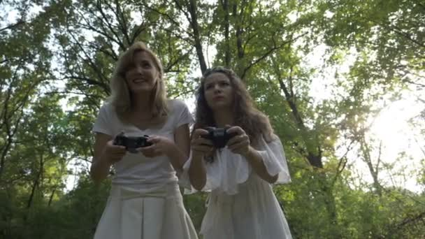 Two young women playing video games outdoor with gamer console joystick