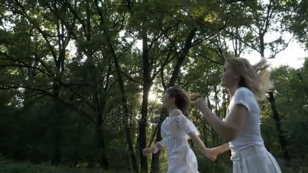 Dvě krásné ženy běh šťastně v přírodě se stromy a slunce v pozadí