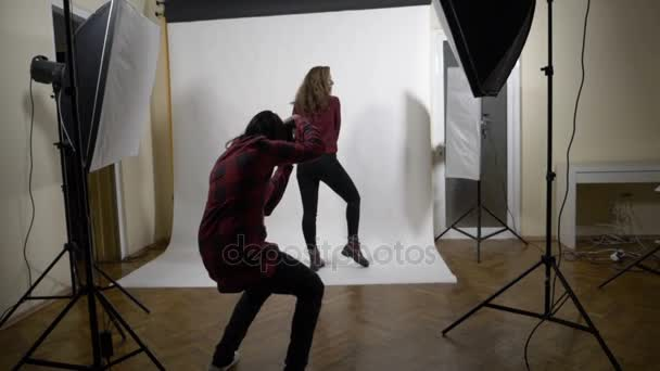 Behind the scenes photo shoot session of a blonde curly slim model for a famous clothing brand in a professional studio with white background in slow motion